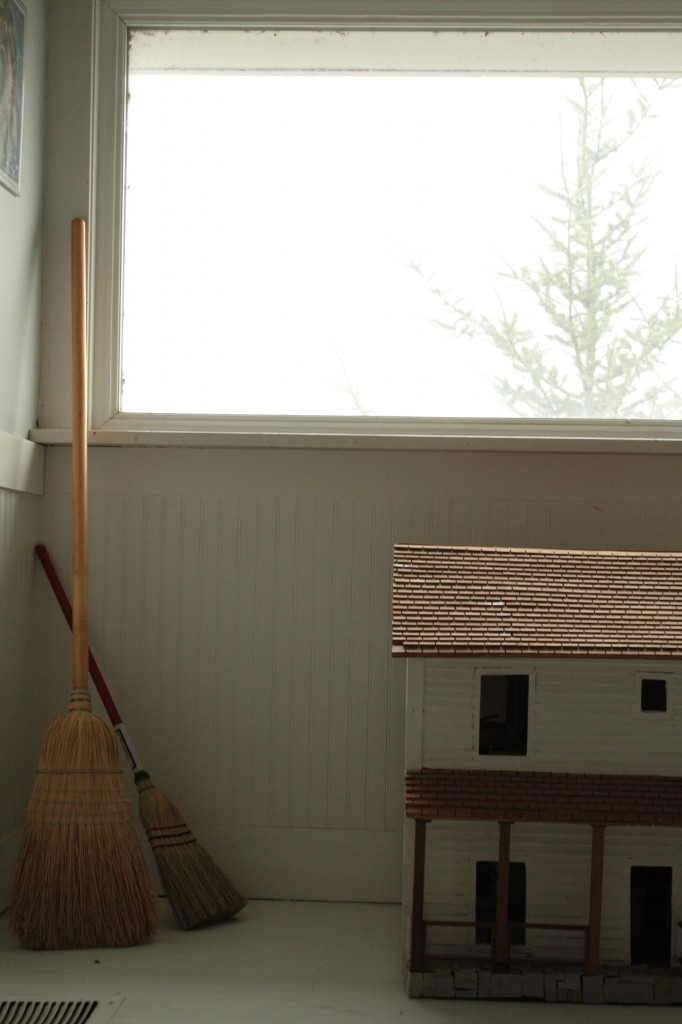 adult and child size brooms in a corner in front of a foggy window and next to a doll house