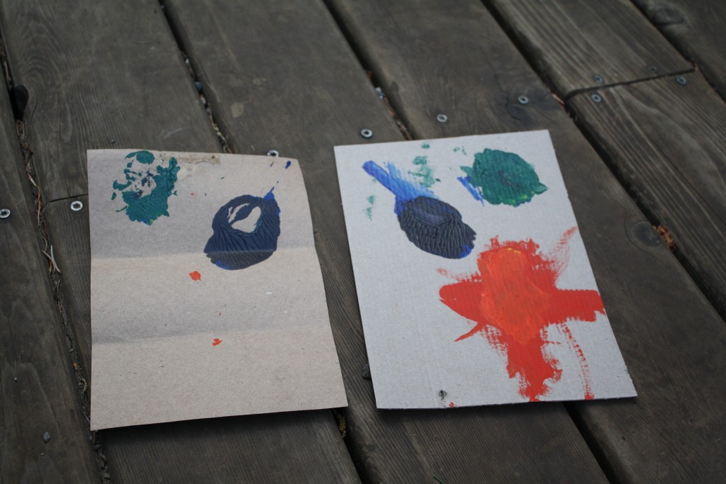cardboard with pools of paint after being used as a palette side-by-side with the print made from the palette at the end of the session