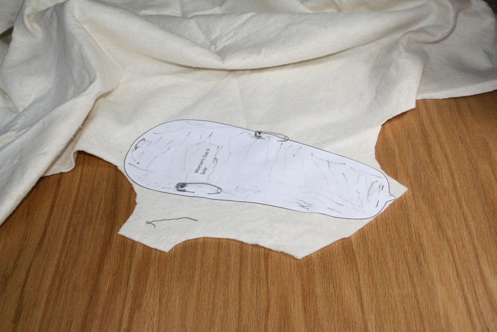 pattern piece pinned to batting for cutting out sole pad for DIY shoes
