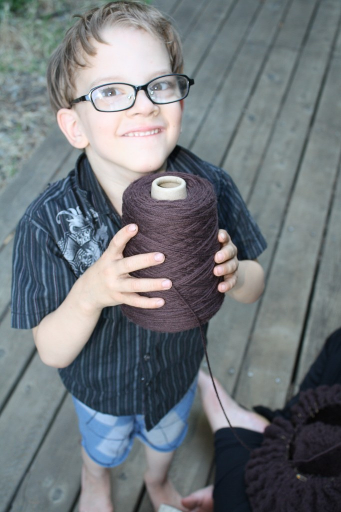 Númenor holding the yarn cone I'm knitting from with my lap (and the WIP in it) in the background