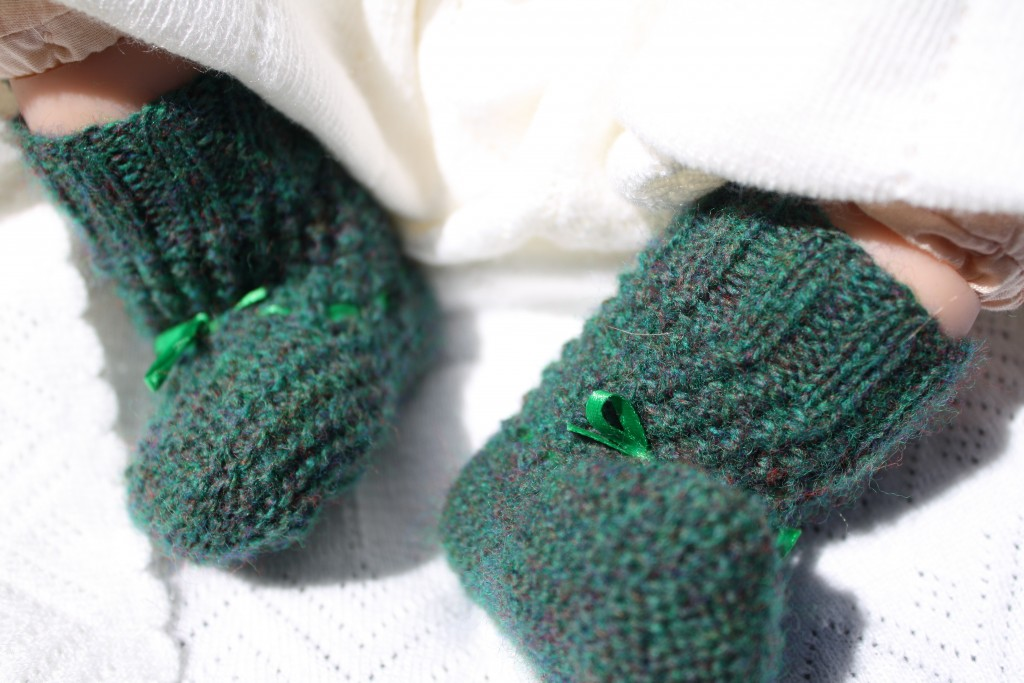 doll wearing handmade knit victorian baby booties