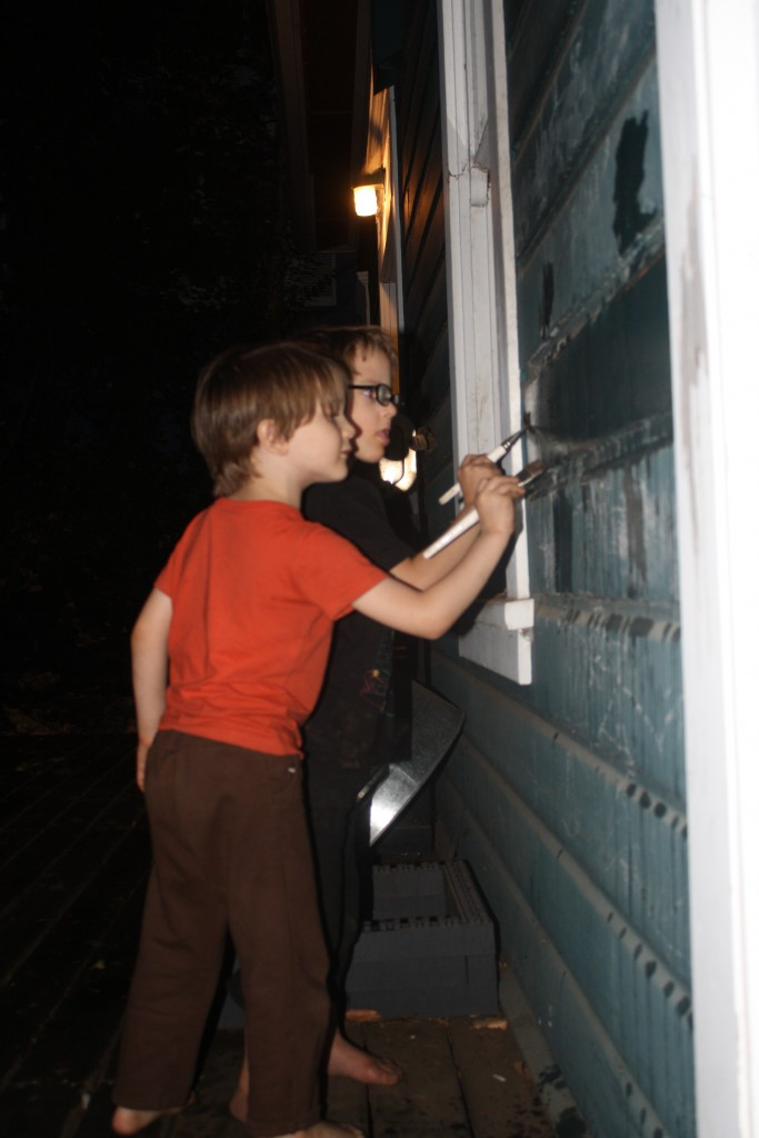 small children painting the side of our house with water in the dusk
