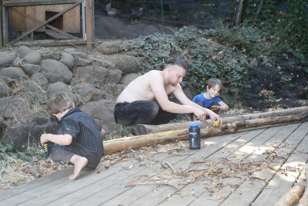 father and small children stripping and measuring logs for crib