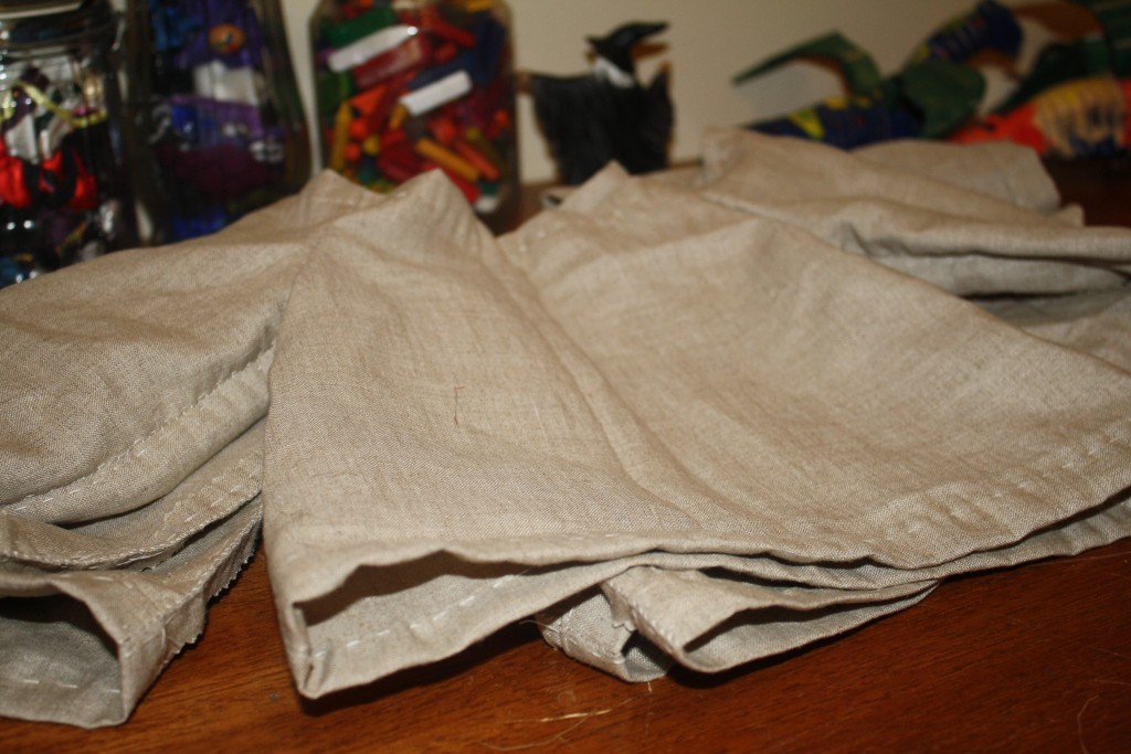 natural linen baby tunics piled up waiting for elastic